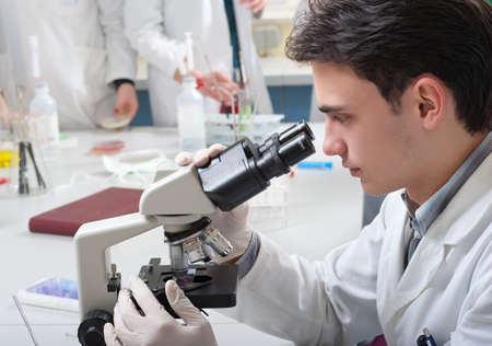 laboratory technician: medical student looking into a microscope