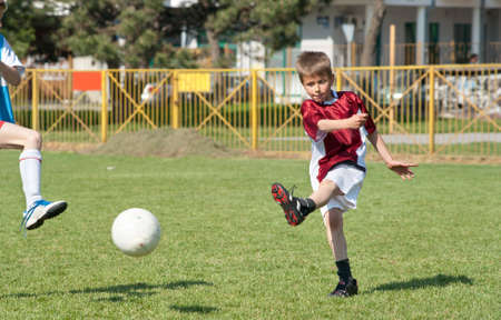 Little Boy playing soccer on the sports field Stock Photo - 10171697