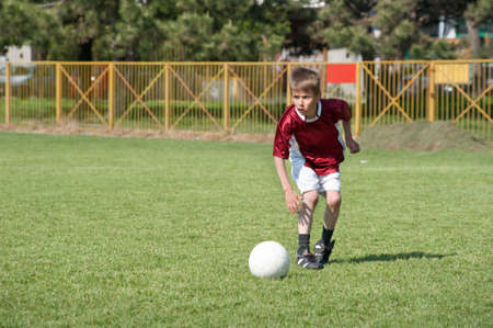 Little Boy playing soccer on the sports field Stock Photo
