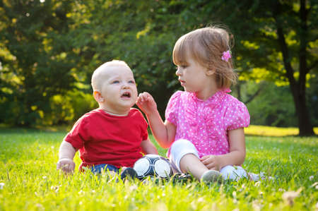 baby sit: brother and sister sitting on the grass