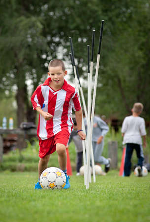 kids' soccer: boy playing with a ball on the soccer field