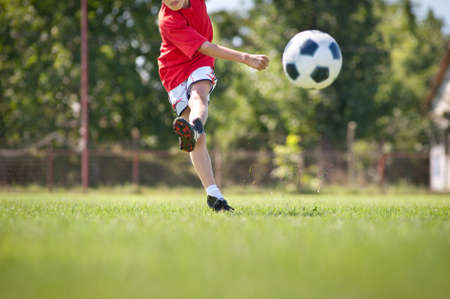 football socks: Little Boy Shooting at Goal Stock Photo