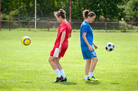 kicking ball: Two young girls playing soccer Stock Photo