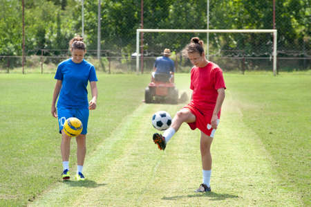 Two young girls playing soccer photo
