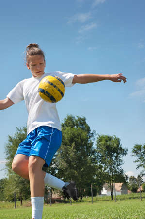 kicking: young girl kicking soccer ball on field
