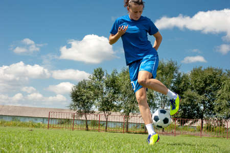 adolescence: young girl kicking soccer ball on field