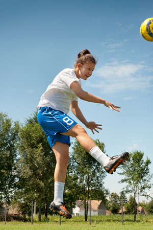 soccer shoes: The girl strikes a head blow to a ball