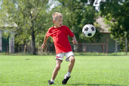 kicking ball: Child playing football on a soccer field