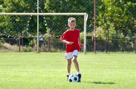 jugando futbol: Ni�o jugando al f�tbol en una cancha de f�tbol Foto de archivo