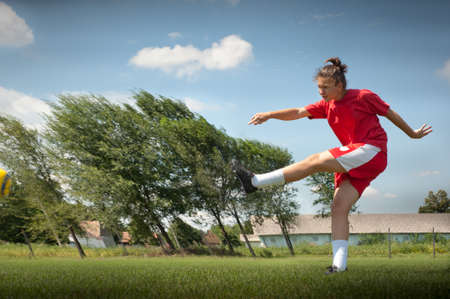 young girl kicking soccer ball on field Stock Photo - 10400687