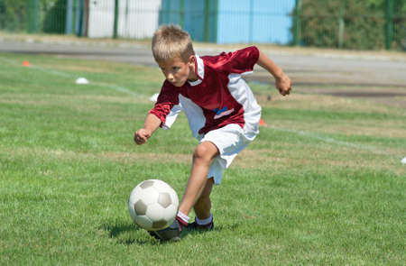 club soccer: Little Boy playing soccer on the sports field Stock Photo