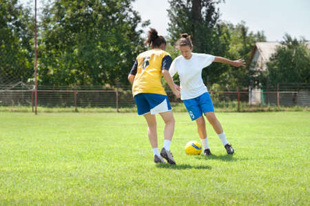 Two young girls playing soccer