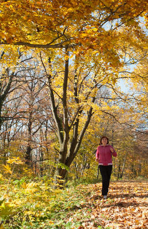 middle-aged woman running through the woods photo