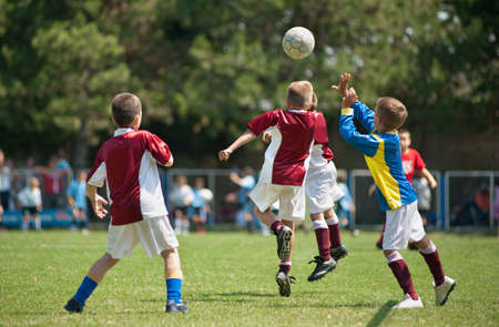 Little Boys playing soccer on the sports field Stock Photo - 11026224