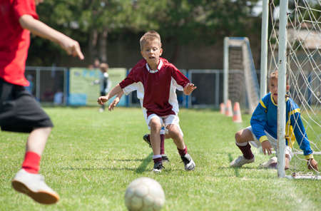 group goals: Little Boys playing soccer on the sports field