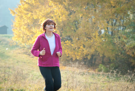 tracksuit: middle-aged woman running through the woods Stock Photo
