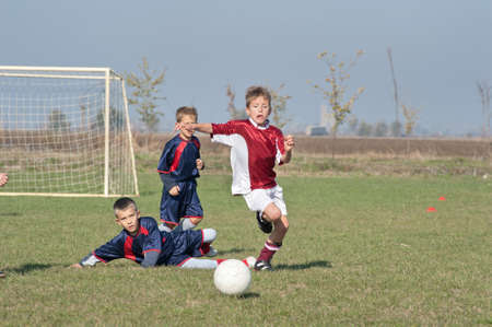boy kicking football on the sports field photo