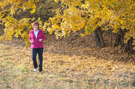 middle-aged woman running through the woods Stock Photo