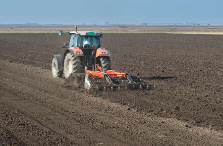 agricultural life: Tractor plowing the fields in spring Stock Photo