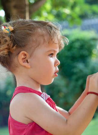 kinderen: Profiel van schattig meisje op zoek naar het in het park