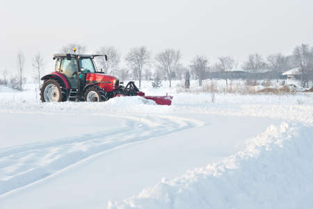 wheeled tractor: Tractor cleaning snow in field