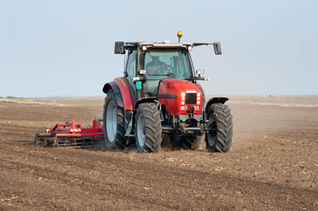 agricultural equipment: Tractor plowing the fields