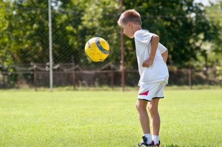 enfant qui joue: Enfant jouant au football sur un terrain de soccer Banque d'images
