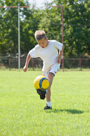 8 years: Child playing soccer on a soccer field