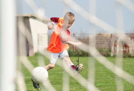 boy kicking a ball at goal photo