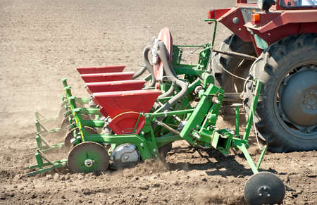 agricultural tools: tractor and seeder planting crops on a field Stock Photo