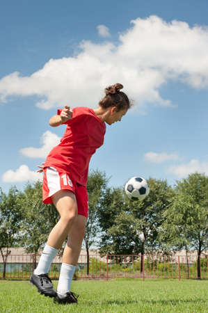 women playing soccer: young girl kicking soccer ball on field