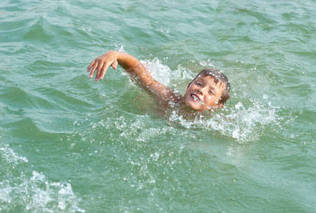 little boy swimming in the pool photo