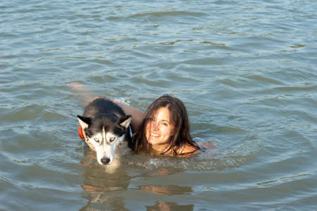 insidious: girl swim with Husky dog Stock Photo