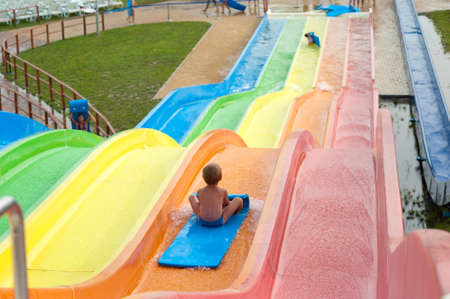 a happy boy falling into water in the aquapark photo