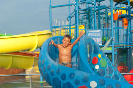 a happy boy falling into water in the aquapark