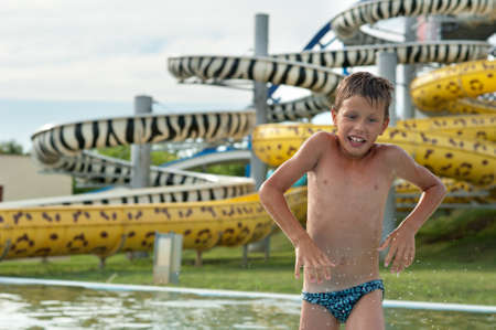 shallow water: a happy boy falling into water in the aquapark