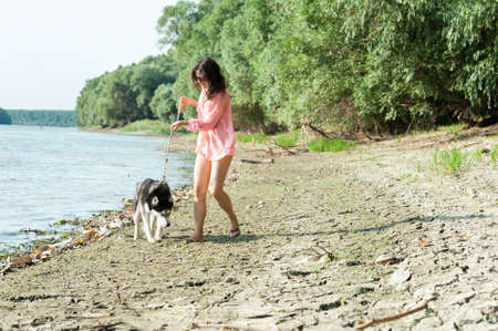 insidious: girl and dog walking along the coast