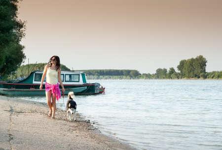 girl and dog walking along the coast photo