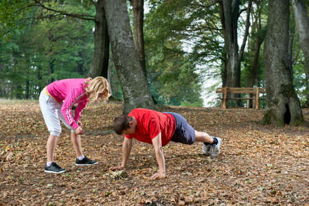 Young couple push-ups in park photo