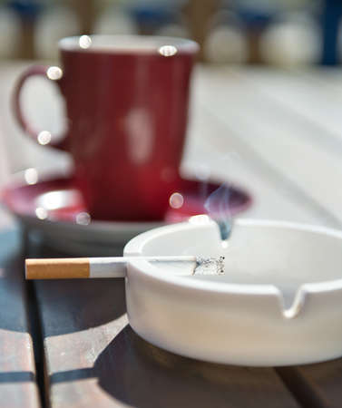 ashtray: burning cigarette in the ashtray  on wooden background Stock Photo