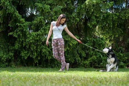 parejas caminando: niña y su fiel perro esquimal siberiano