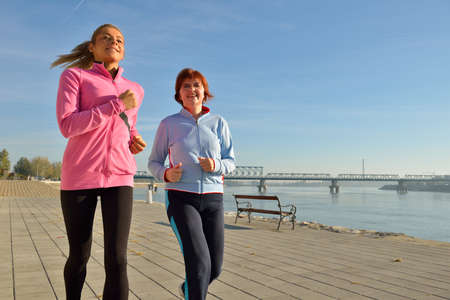 outdoor pursuit: Mother and daughter jogging on coasts