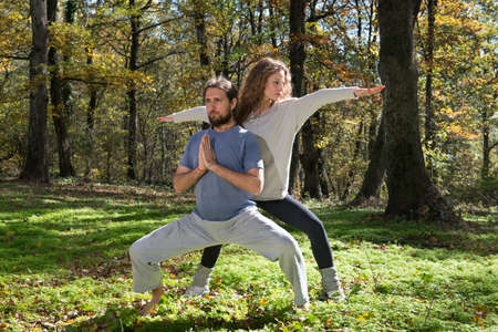family garden: girl and man doing yoga meditation in a forest