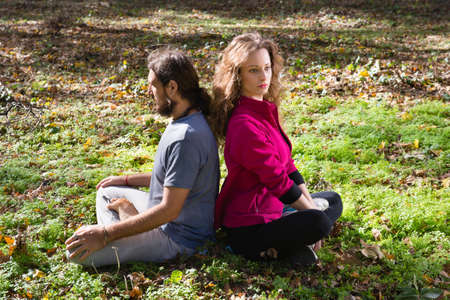 girl and man doing yoga meditation in a forest photo