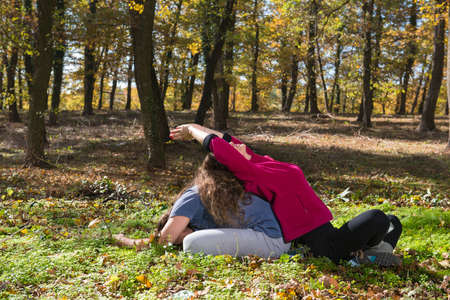 Couple doing yoga meditation in a forest photo