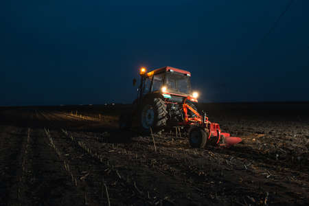 wheel tractor: Tractor plowing at night