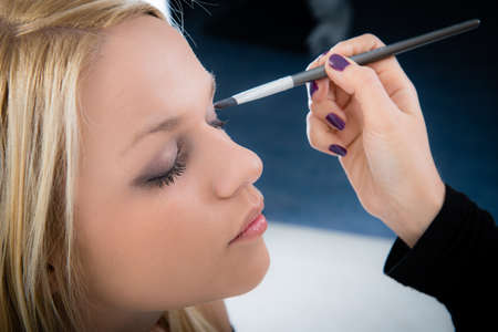 girl applying make-up by make-up artist photo