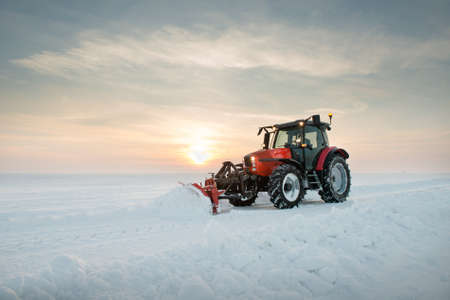 Tractor cleaning snow in field photo
