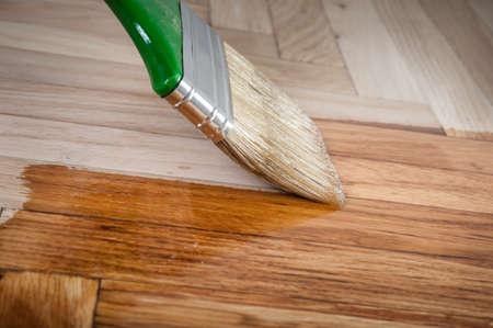 home construction: Varnish brush strokes on a wooden floor Stock Photo