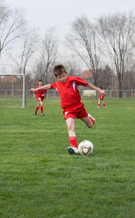 jugando futbol: chico patadas de fútbol en el campo de deportes